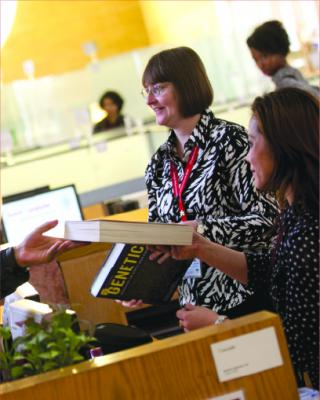 Image of CMU students interacting with librarian.