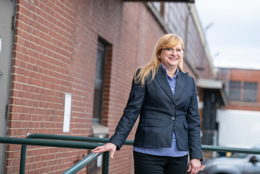 Ann Marie Mesco standing next to brick wall