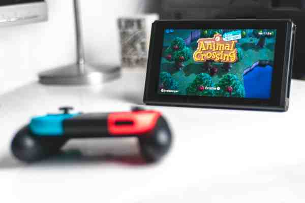 A Nintendo Switch and controller on a white table with Animal Crossing: New Horizons on the screen.